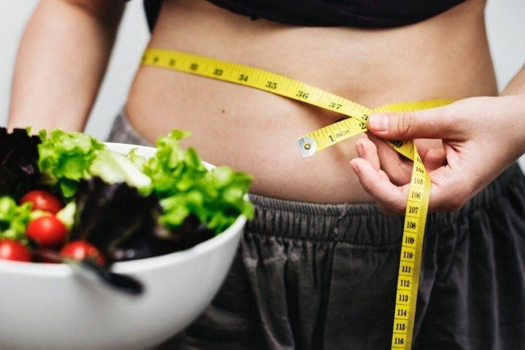 Jak schudnąć z brzucha - kobieta mierzy swoje obwody