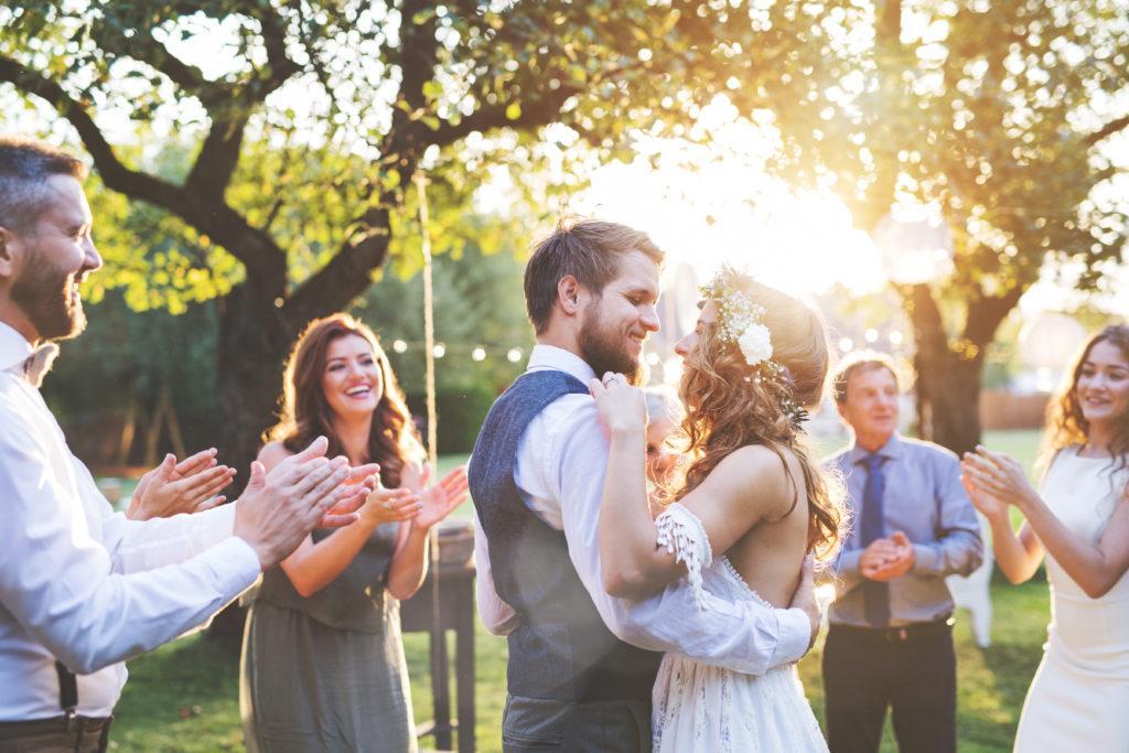 Para młoda tańczy w ogrodzie do polskiej piosenki na pierwszy taniec