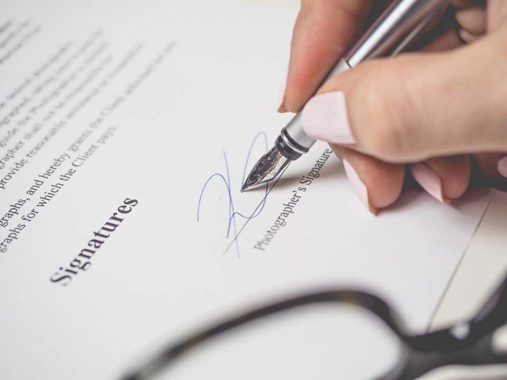 Kobieta podpisuje dokumenty o kredyt na wesele