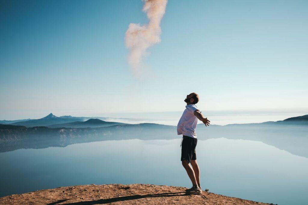 Mężczyzna nad jeziorem po przeczytaniu cytatów o szczęściu