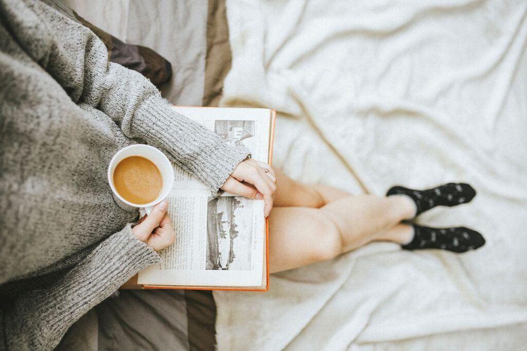 Dziewczyna trzyma kubek i książkę z cytatami o kobietach