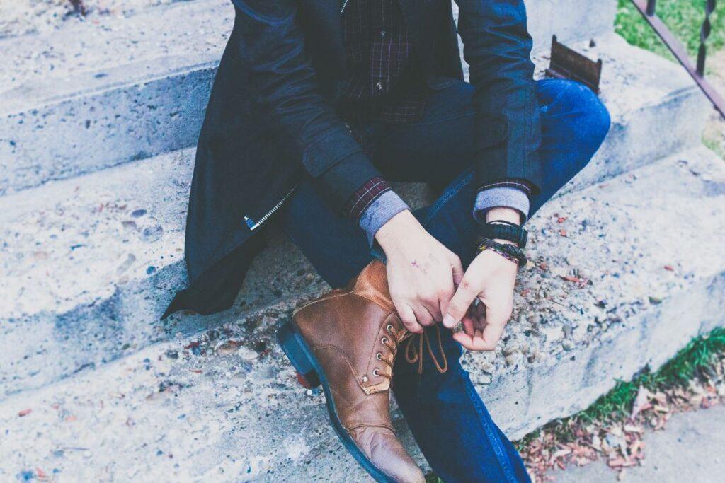 mężczyzna wiąże buty do granatowego garnituru