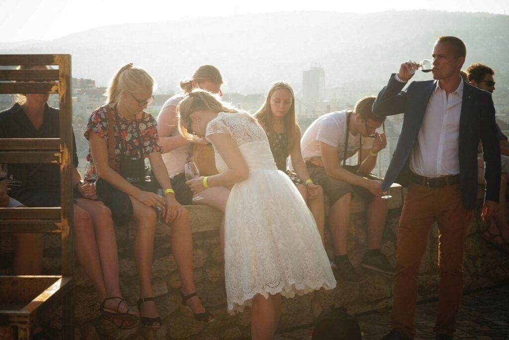 Para młoda z gośćmi piją wino