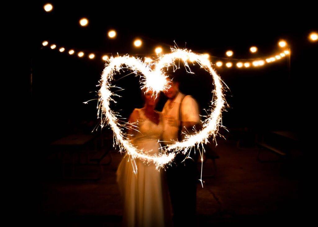 Para młoda robi serce zimnymi ogniami na weselu