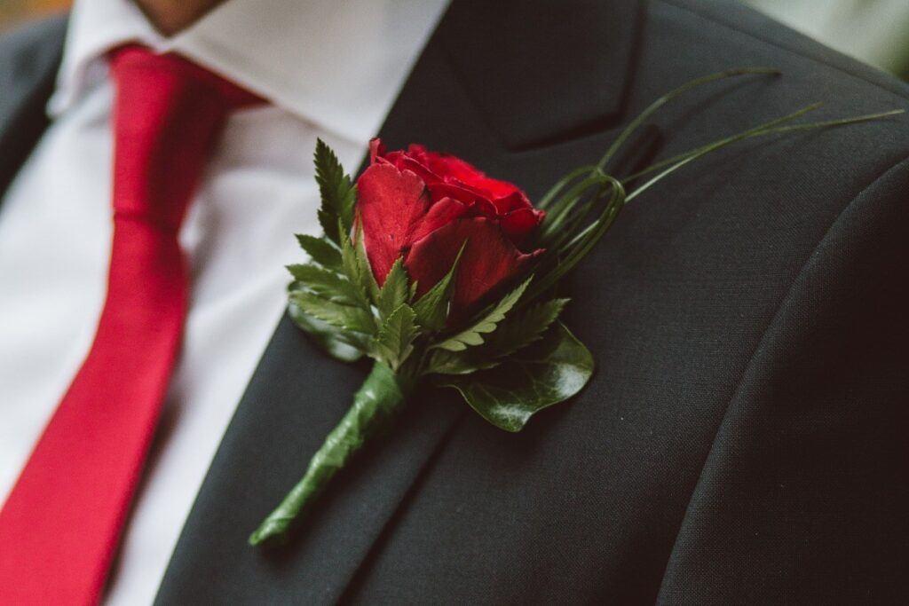 czerwona róża w butonierce w zestawie z czerwonym krawatem