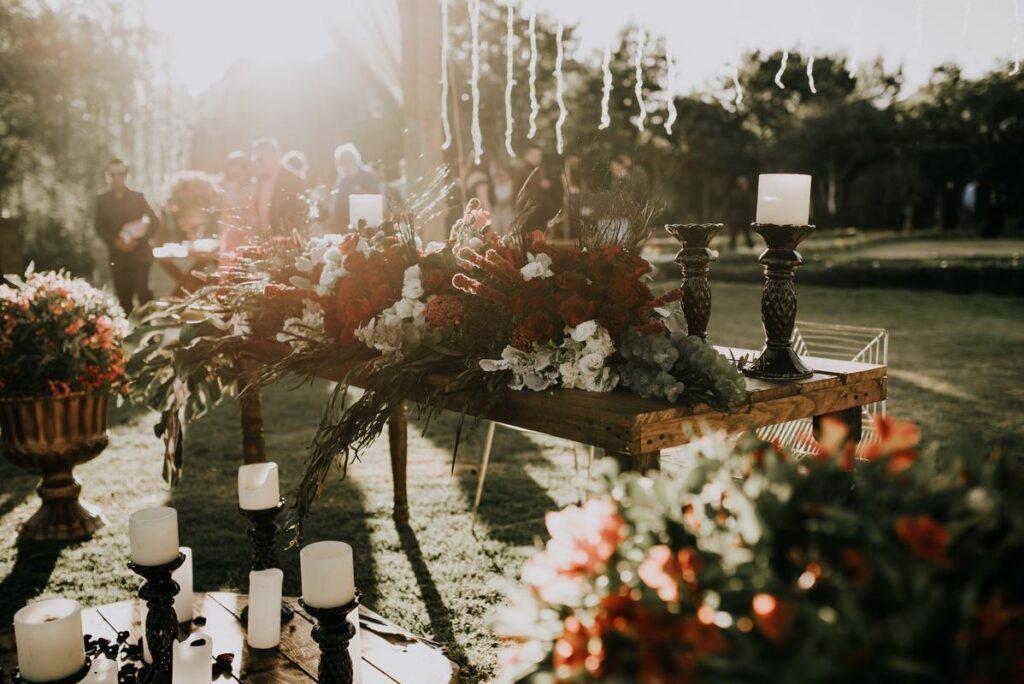 Stół z kwiatami i świecami przygotowany na wesele w ogrodzie