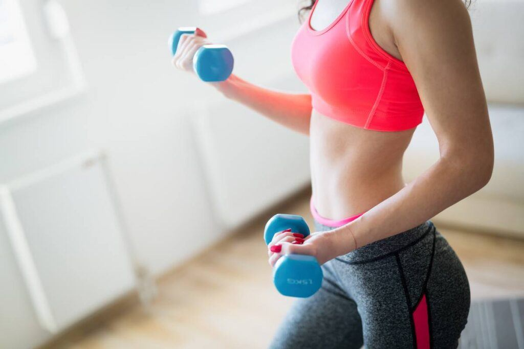 Kobieta pokazuje, jak ćwiczyć w domu z hantlami