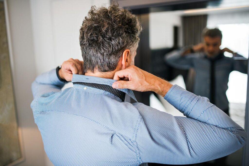 Wiązanie krawata przez mężczyznę przed lustrem