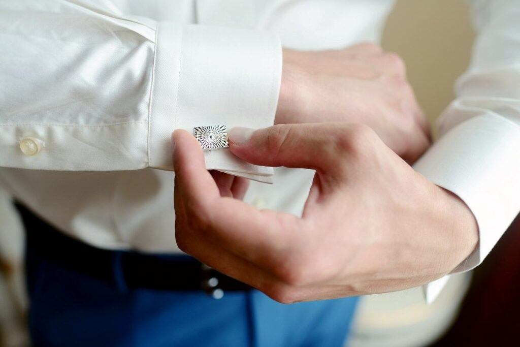 Mężczyzna pokazuje, jak zapiąć spinki do mankietów