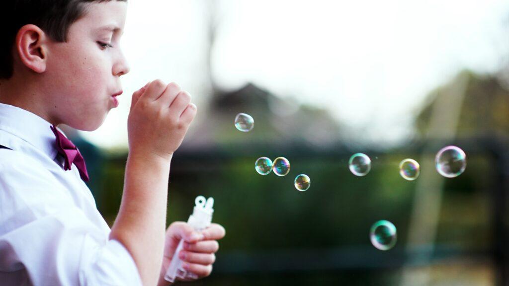 chłopiec elegancko ubrany puszcza bańki mydlane