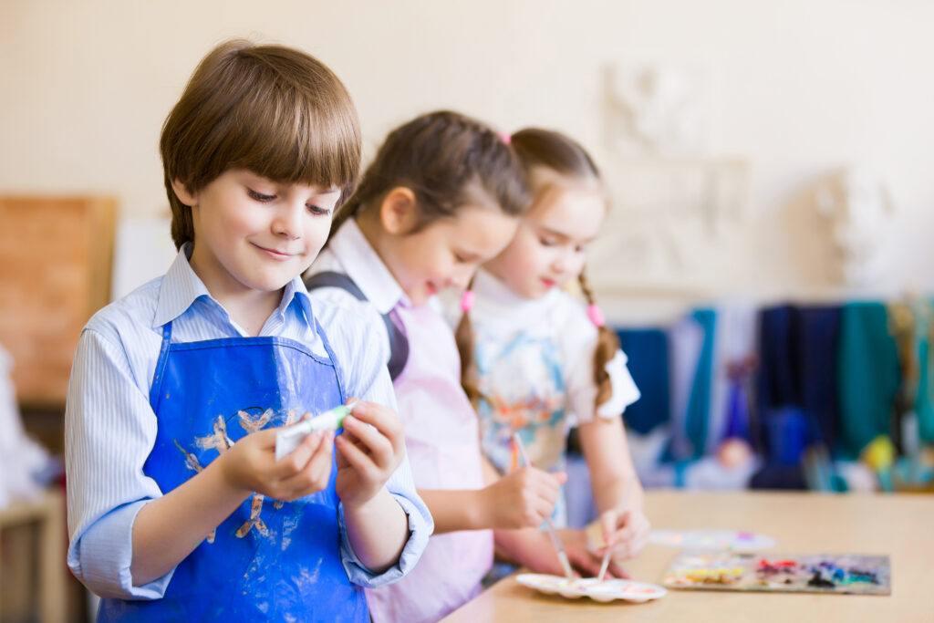 Grupa dzieci wykonująca rysunki plastyczne i slime