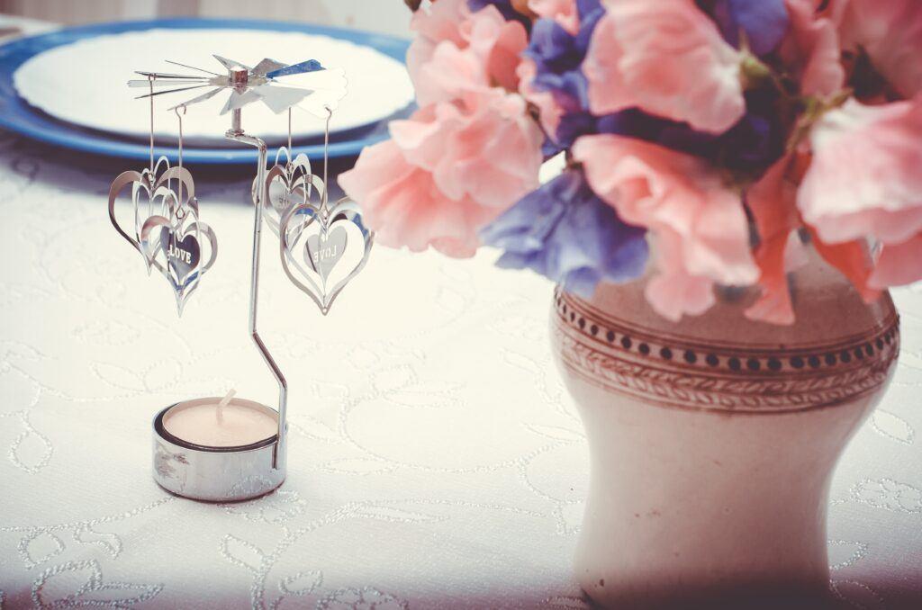 udekorowana świeczka i kwiaty na stole weselnym