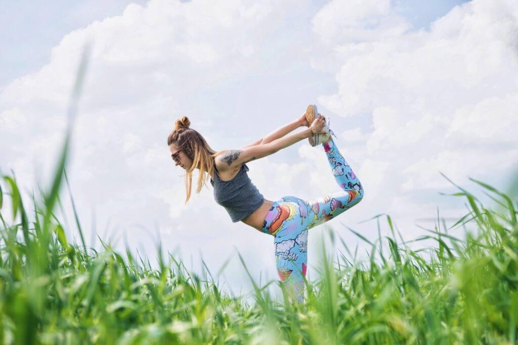 kobieta ćwiczy jogę na łące