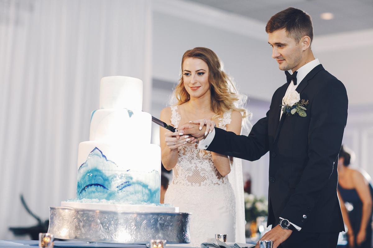 Panna Młoda i Pan Młody podczas krojenia tortu weselnego