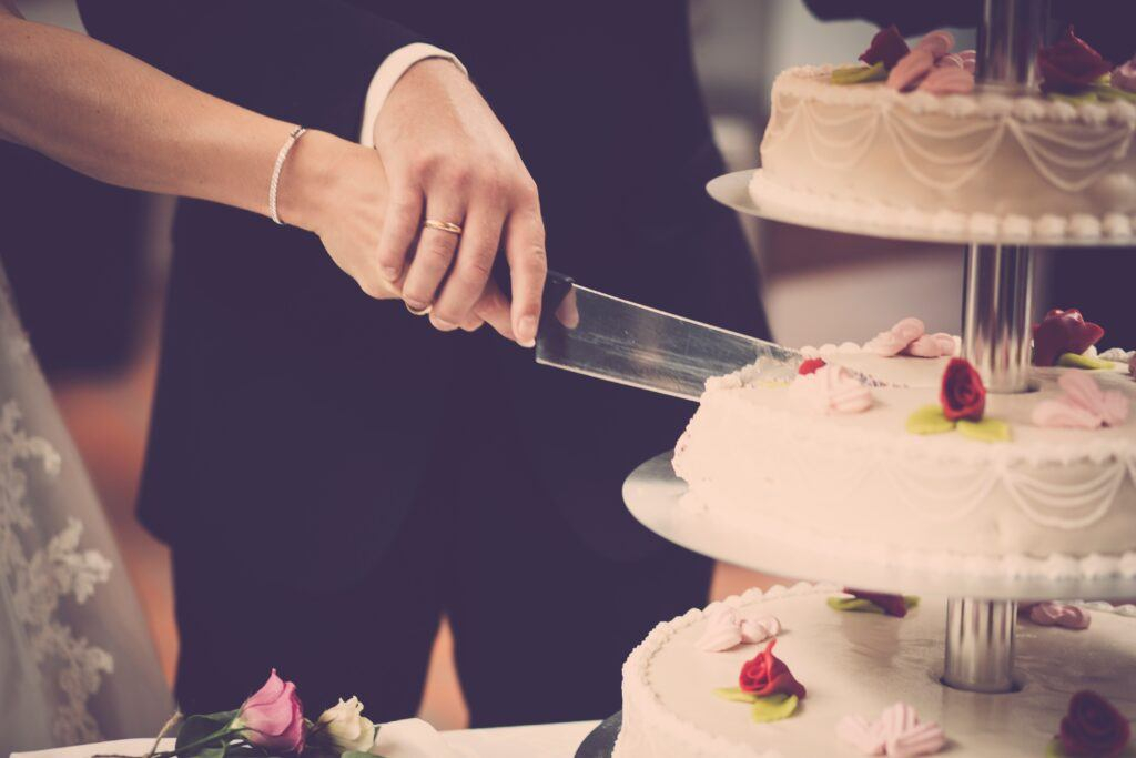 Para Młoda krojąca swój tort weselny podczas przyjęcia