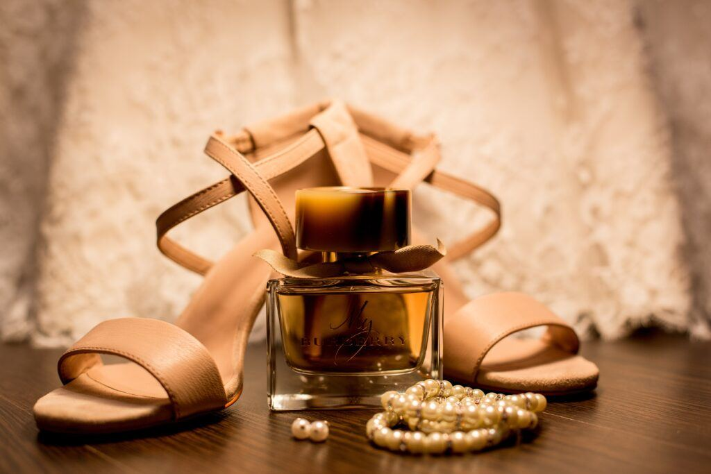 beżowe sandały ślubne stojące obok flakonu perfum i biżuterii