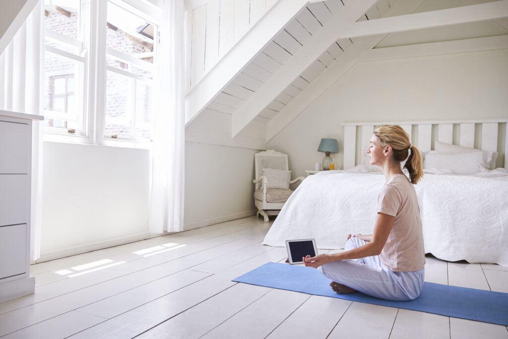 młoda kobieta medytująca w domu