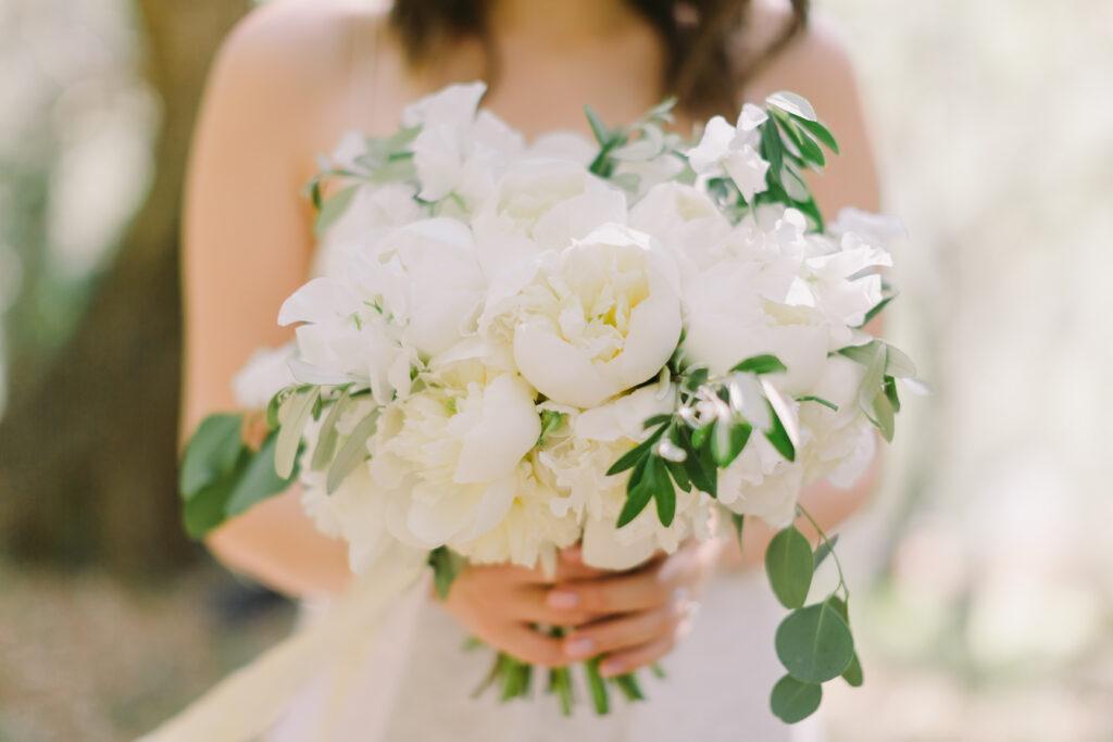 panna młoda trzymająca w ręku piękny bukiet z białych kwiatów