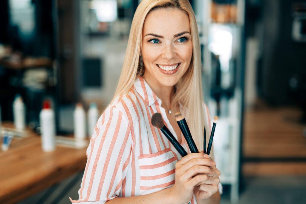 kobieta trzymająca w ręce pędzle do makijażu