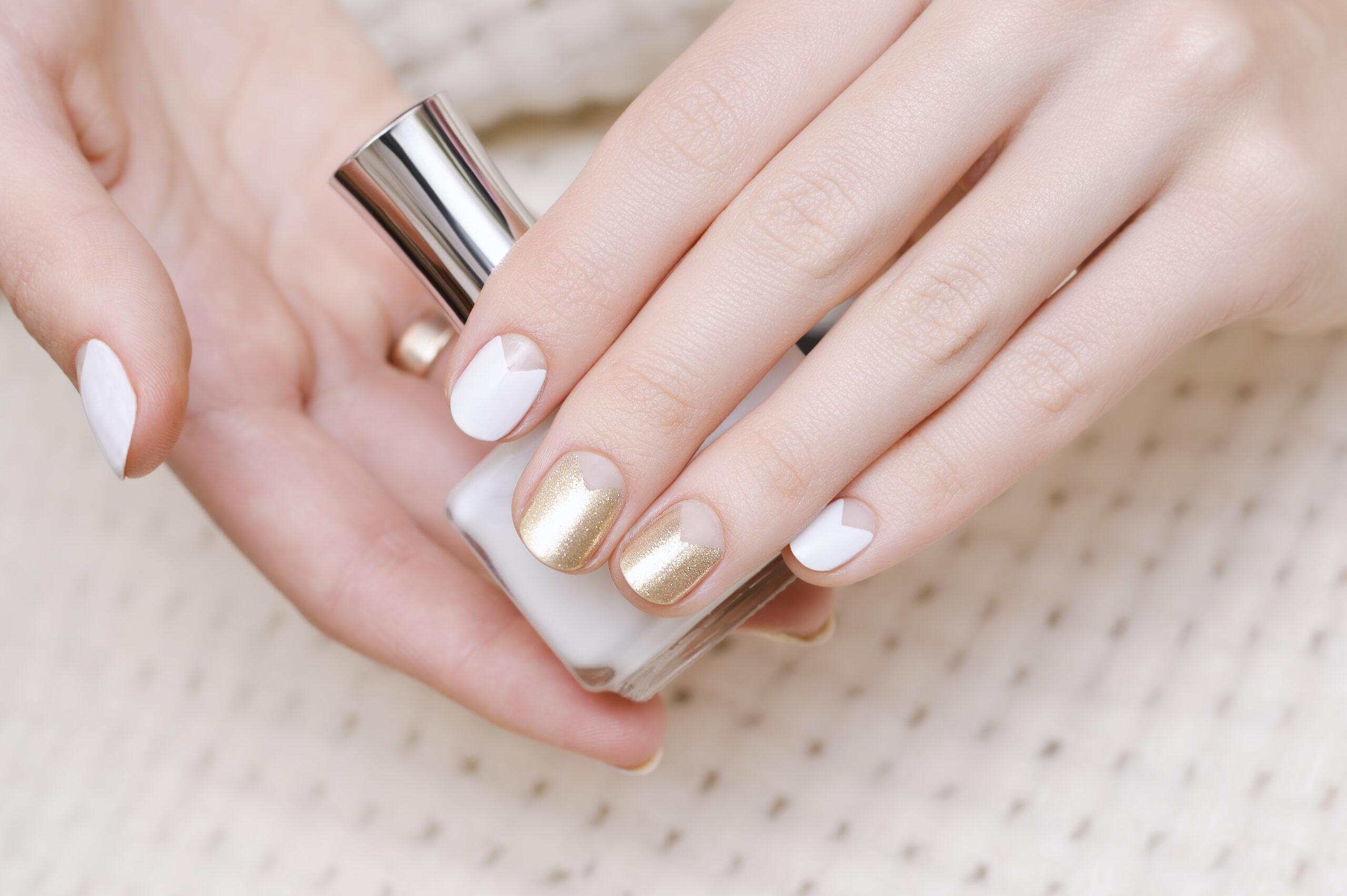 Dłonie kobiety z manicure w kolorze bieli i złota