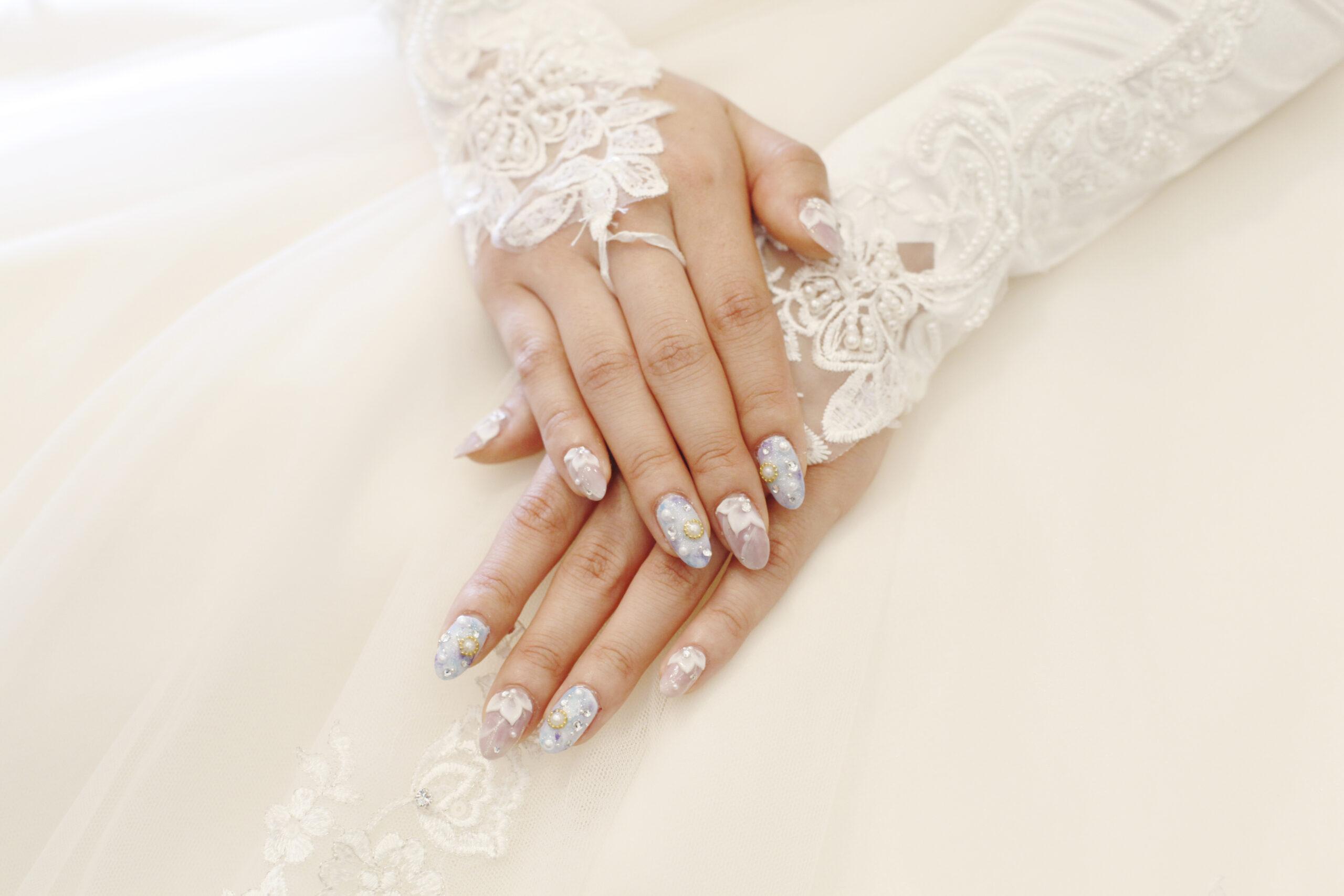 delikatne perłowe paznokcie na ślub z ozdobami na dłoniach panny młodej