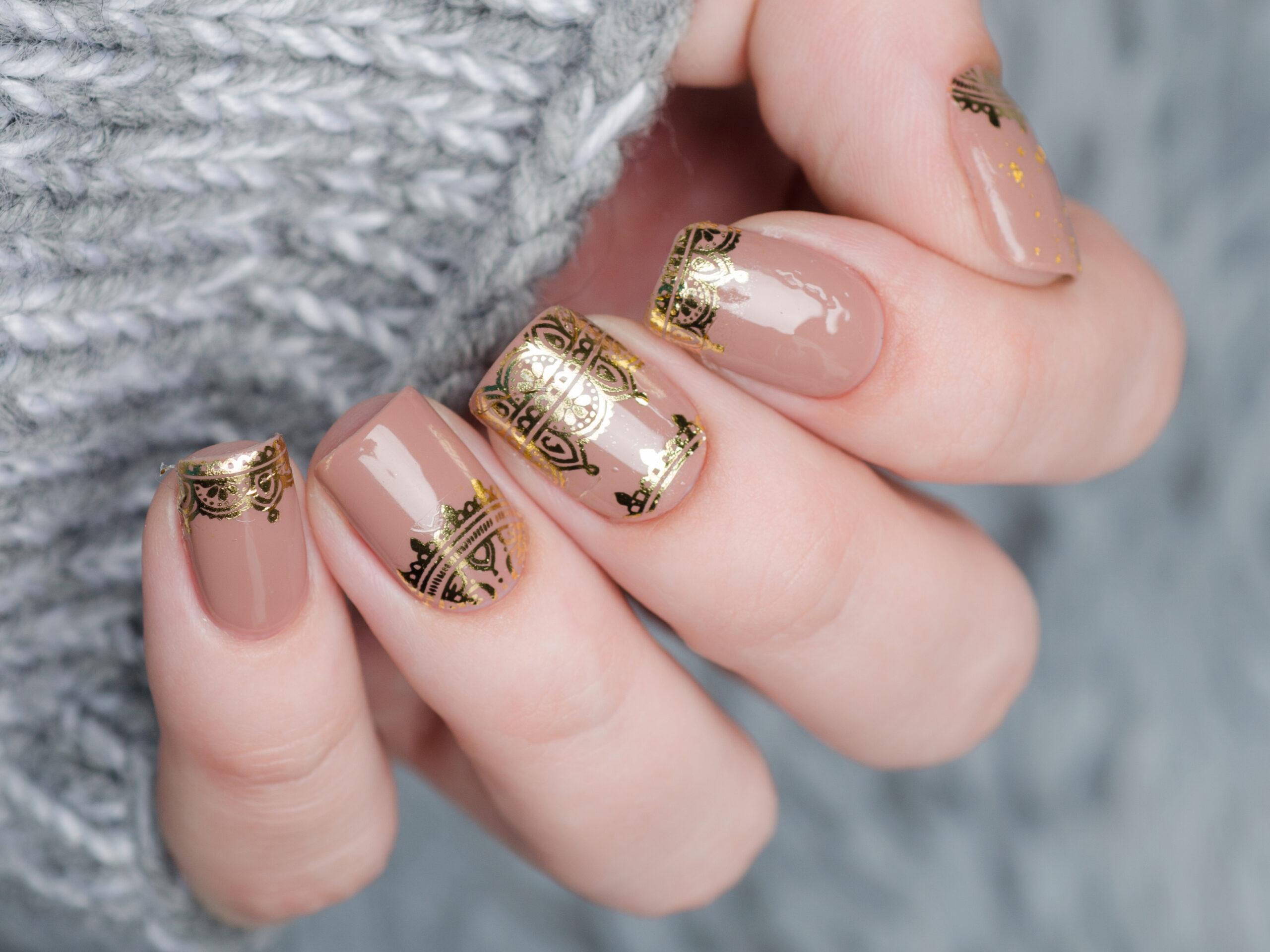 ślubne paznokcie nude ze złotymi wzorkami