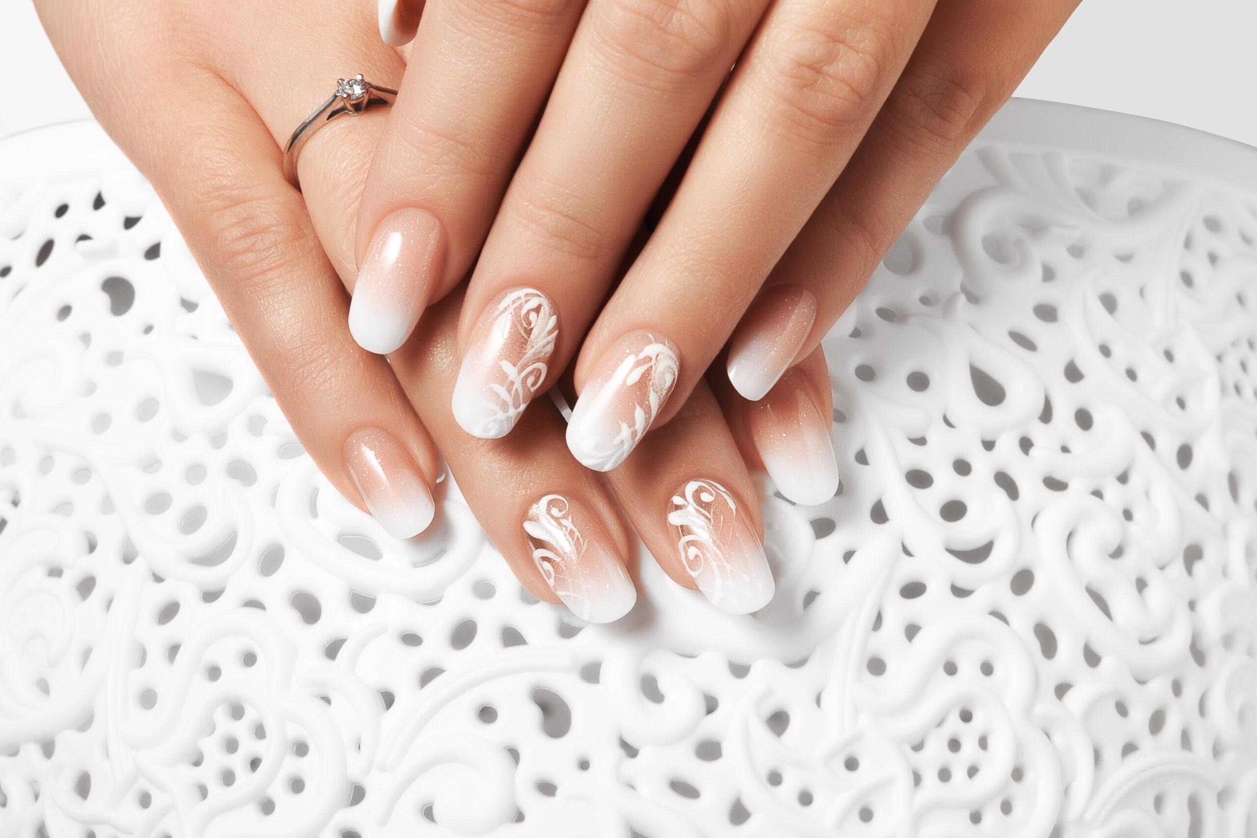paznokcie ślubne w białe wzory na dłoniach panny młodej