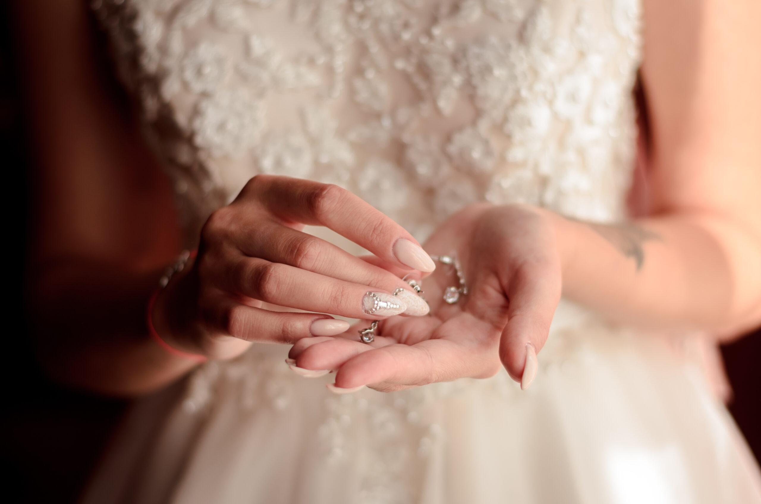 paznokcie ślubne nude z ozdobnymi cyrkoniami na dłoniach panny młodej