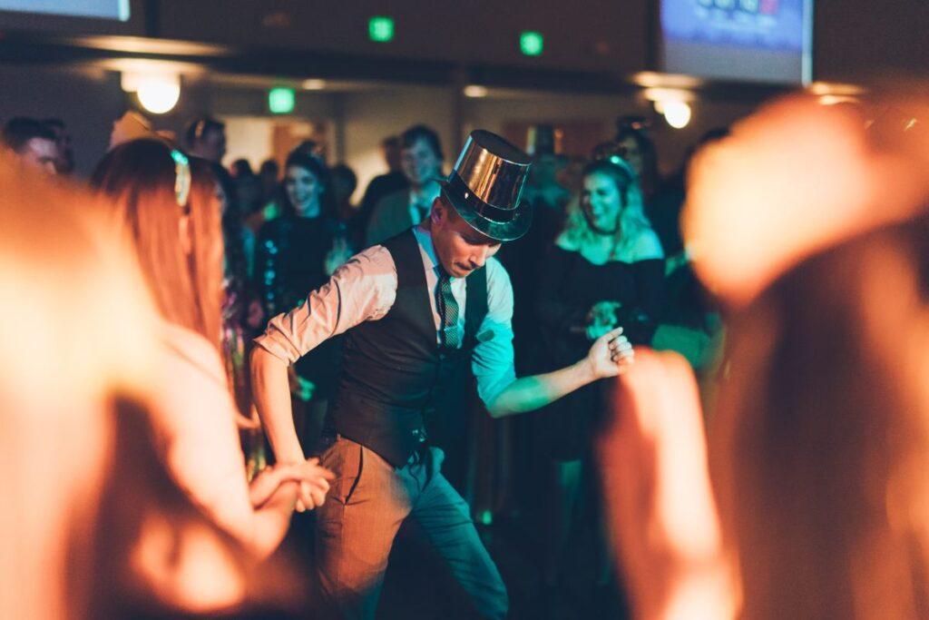 zabawy weselne - zaproszony gość tańczy w srebrnym kapeluszu