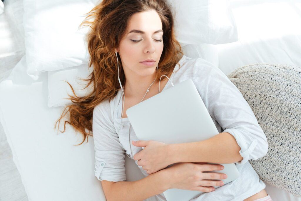 Kobieta śpi na łóżku z laptopem w ręce