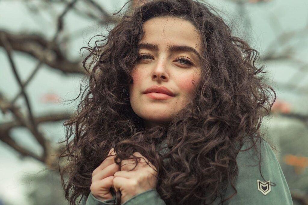 Kobieta z kręconymi włosami - jak przyspieszyć porost włósów