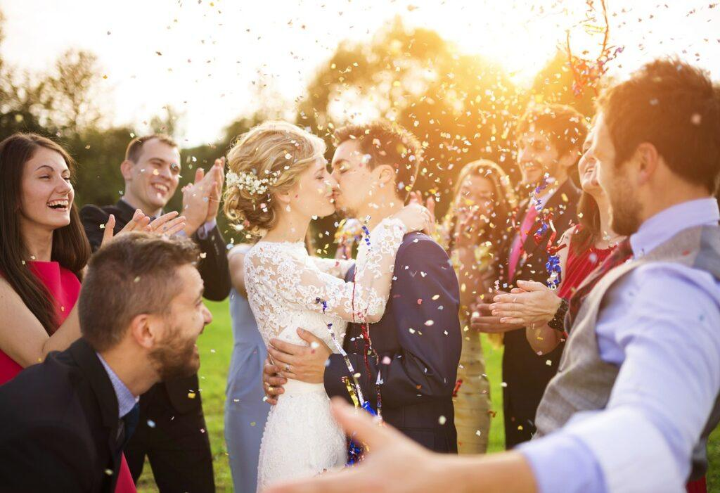 Para młoda całuje się podczas śpiewania przyśpiewek weselnych