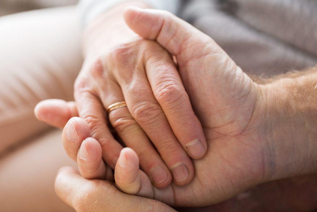 Małżeństwo trzyma się za ręce podczas odnawiania przysięgi małżeńskiej
